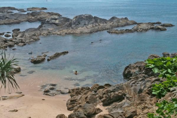 תמונת חוף קאלים מלא בריכות שחייה קטנות ורדודות